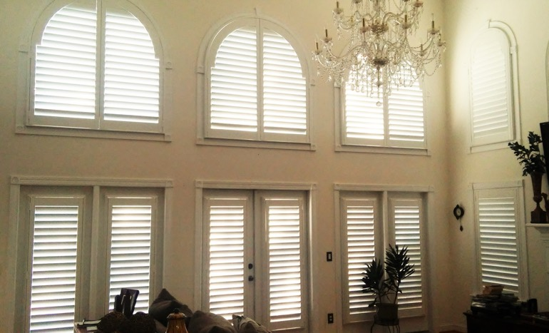 Great room in two-story Detroit home with plantation shutters on arch windows.
