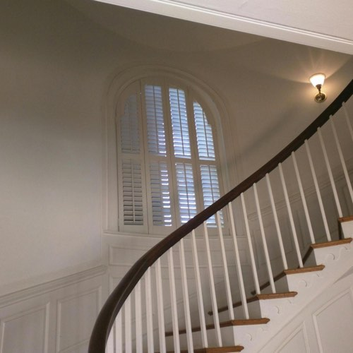 White plantation shutters adorning rounded window located in round stairwell.