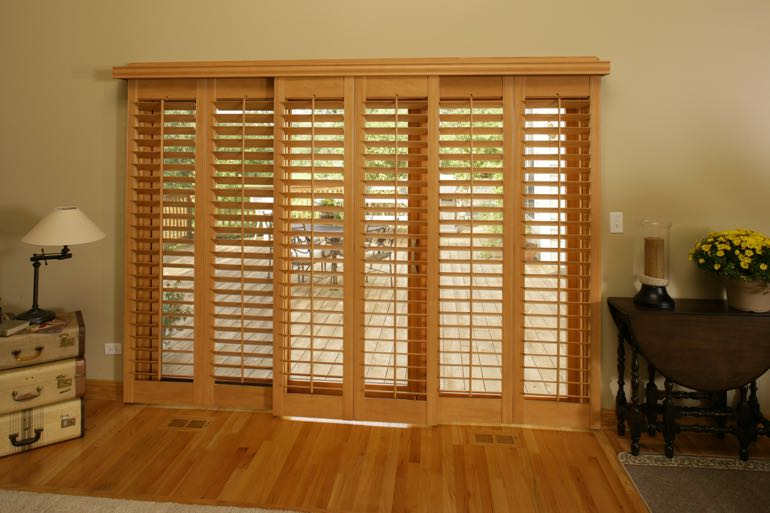 plantation shutters on sliding door leading to back porch.