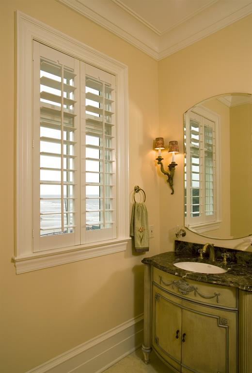 White shutters in a light bathroom looking out over ocean