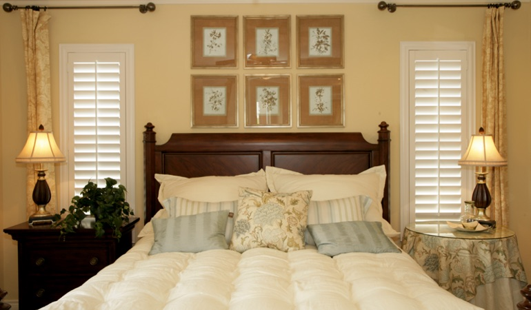Tall plantation shutters framing bed in a bedroom in Detroit