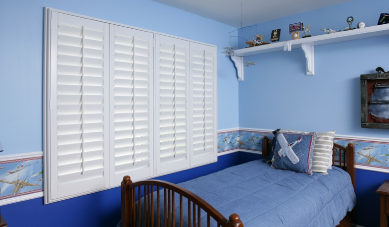 Large plantation shutters covering window in blue kids bedroom in Detroit